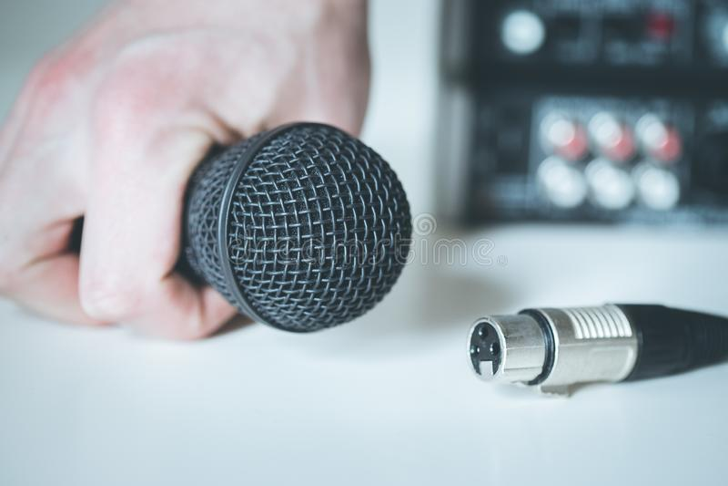 Microfone preto que guardam à disposição, e cabo audio, misturador no fundo obscuro fotos de stock royalty free