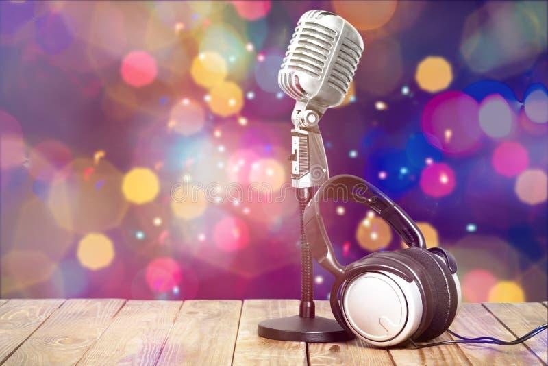 Microfone retro e fones de ouvido do estilo em de madeira imagem de stock royalty free