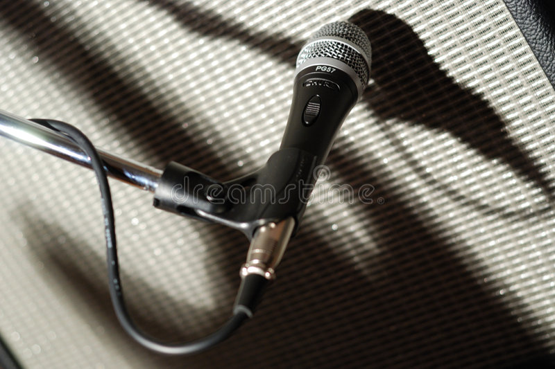 Microfone and guitar shadow. Recording microphone closeup on an amplifier with electric guitar shadow royalty free stock photos