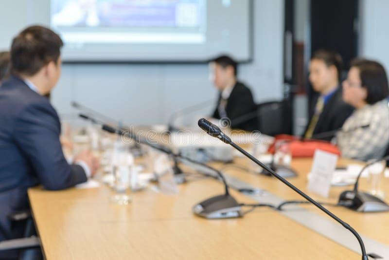 Microfones da conferência na tabela sobre abstrato borrada do participante na sala de reunião imagens de stock