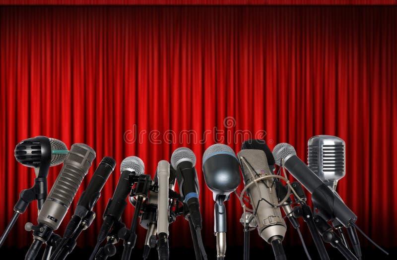 Microfoni davanti alla tenda rossa fotografia stock