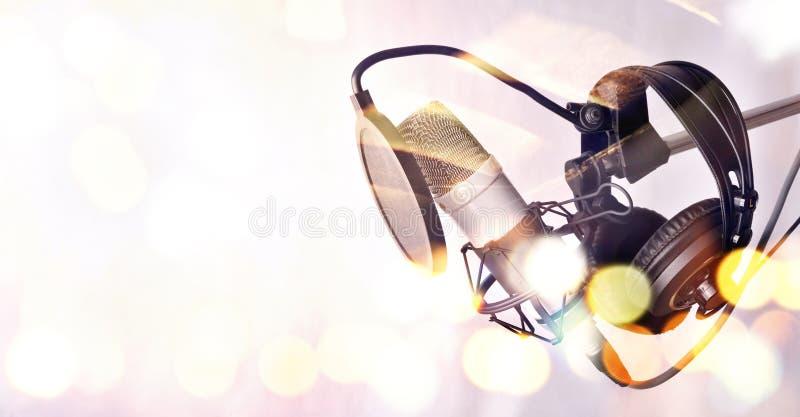 Microfono a condensatore ed attrezzatura dello studio dietro un vetro immagine stock
