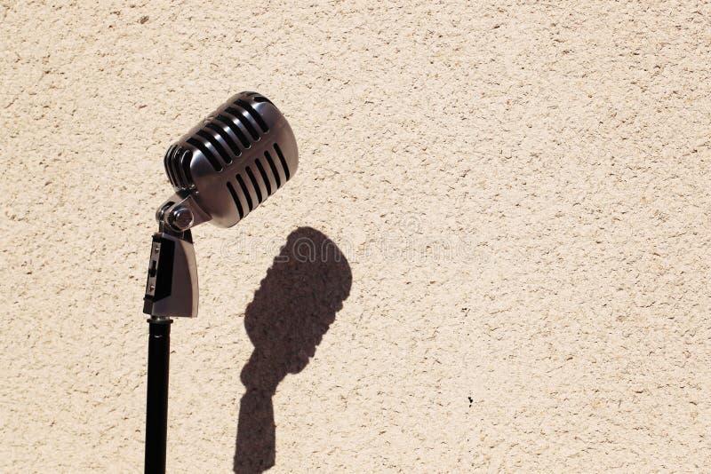 Microfono d'annata d'argento nello studio sul fondo della parete immagini stock