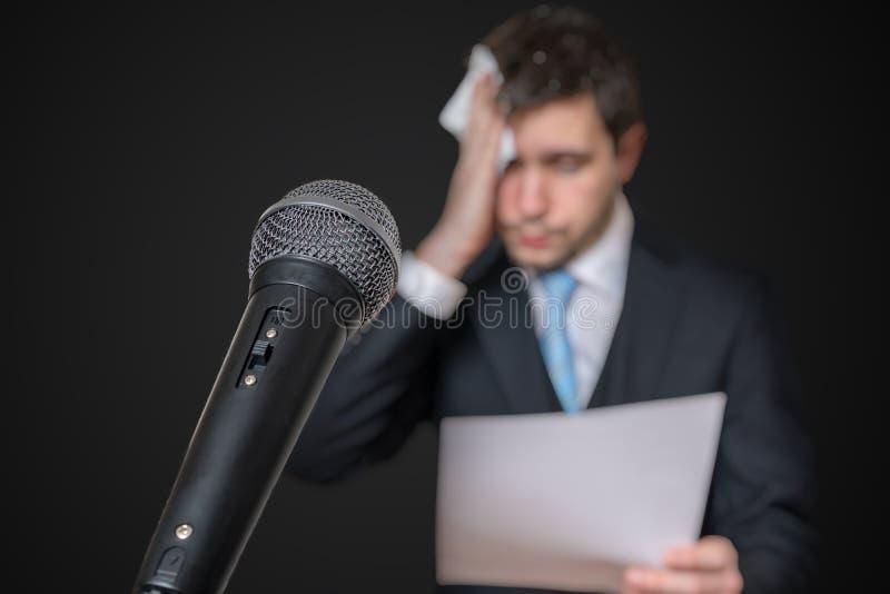 Microfono davanti ad un uomo nervoso che è impaurito di discorso e di sudorazione pubblici immagine stock libera da diritti