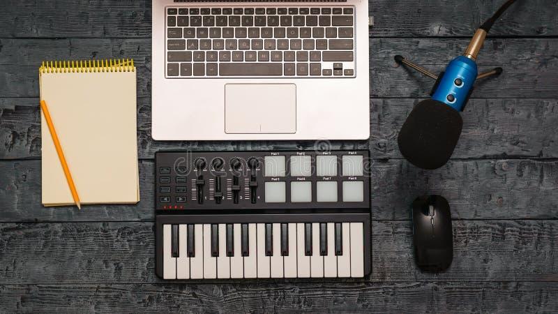 Microfono del miscelatore, del computer portatile, della matita e del cavo di musica elettronica su una tavola di legno nera Attr immagine stock libera da diritti