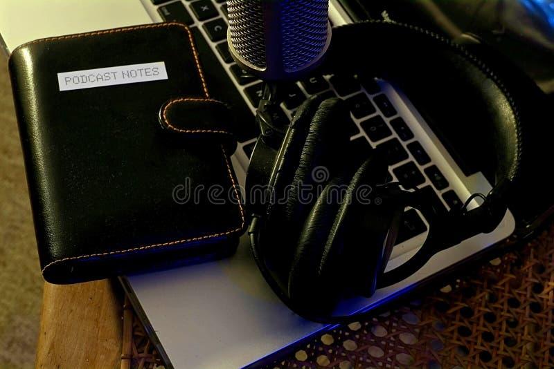 Microfono di podcast sopra un computer portatile con le note e le cuffie immagine stock