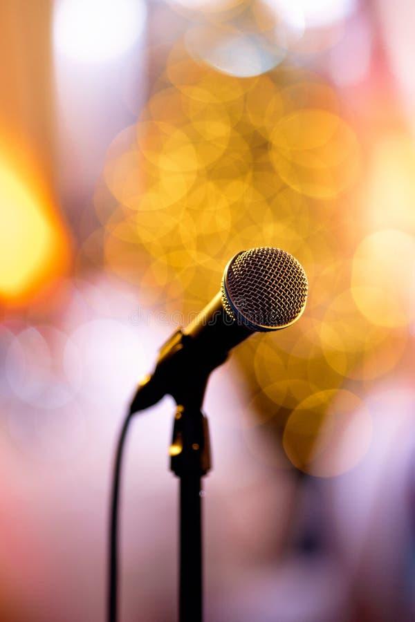 Microfono isolato del bokeh su una fase di concerto con gli artisti redy da eseguire nel dietro le quinte fotografie stock libere da diritti