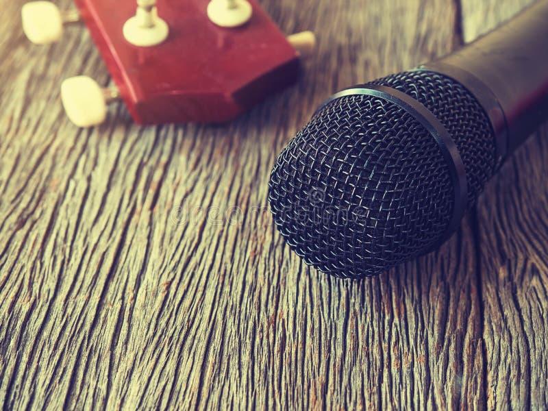 Microfono nero sul piatto di legno con la chitarra dentro dalle sedere del fuoco immagine stock libera da diritti