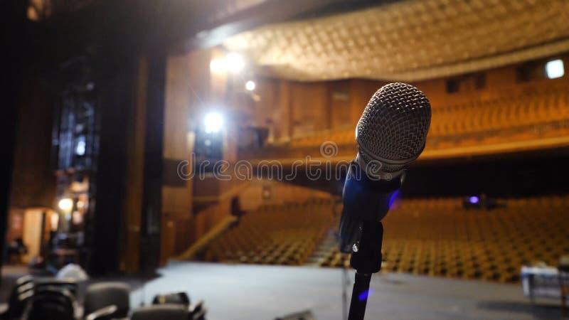 Microfono sulla fase e corridoio vuoto durante la ripetizione Microfono in scena con le fase-luci nei precedenti immagini stock libere da diritti