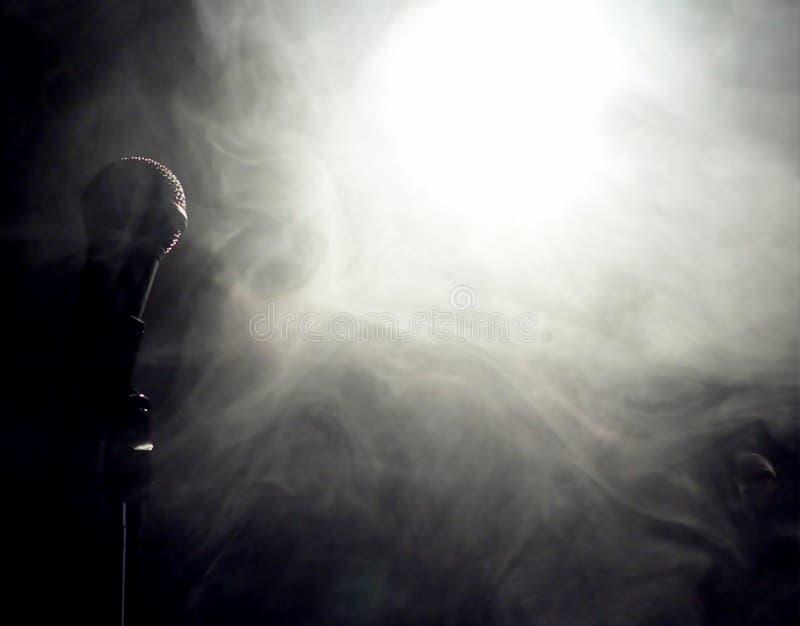 Microfoon bij rand van rook en mist in licht stock foto