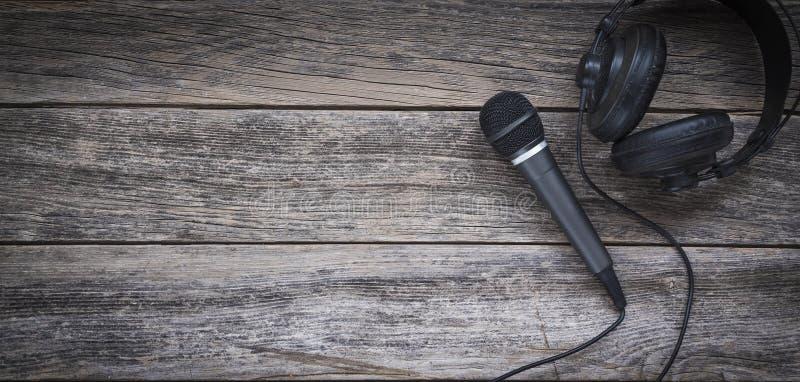 Microfoon en hoofdtelefoon op een houten achtergrond stock foto's