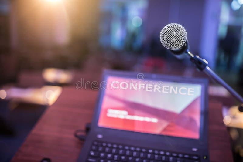Microfoon en laptop computer bij podium op bedrijfsseminarie in conferentieruimte stock afbeeldingen