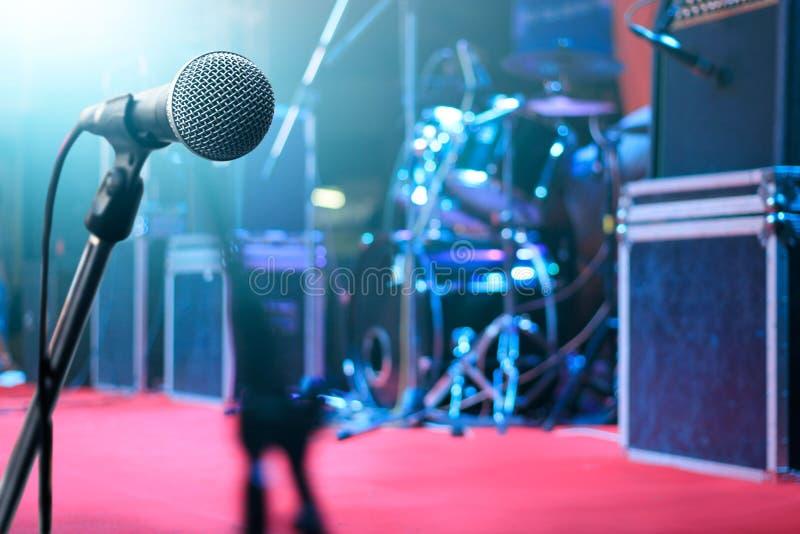 Microfoon en muziekinstrument op stadiumachtergrond stock afbeeldingen