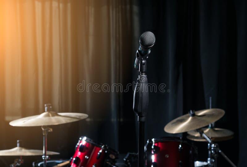 Microfoon en trommels op donkere achtergrond stock foto