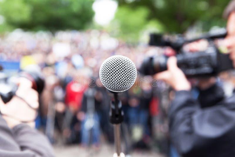 Microfoon in nadruk bij straatprotest, vage cameraman en fotograaf op achtergrond stock fotografie