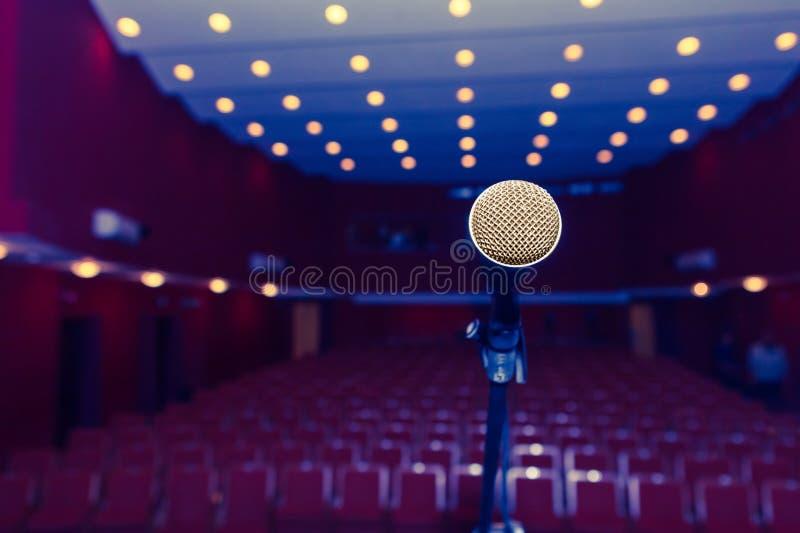Microfoon op een achtergrond van donkere zaal met plaatsing voor toeschouwers stock foto