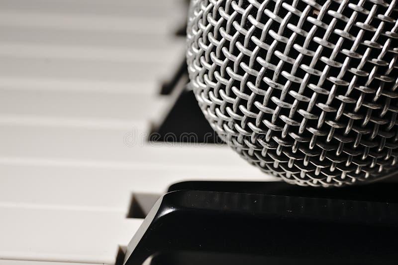 Microfoon op een pianotoetsenbord stock afbeeldingen