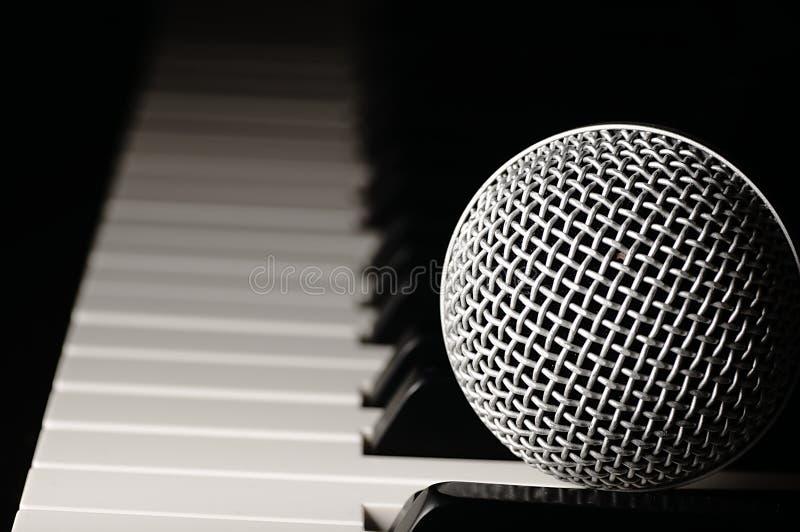 Microfoon op een pianotoetsenbord stock afbeelding
