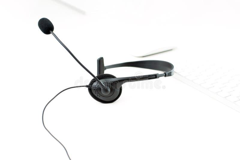 Microfoonhoofdtelefoon op witte lijst met het toetsenbordachtergrond van de onduidelijk beeldcomputer stock foto