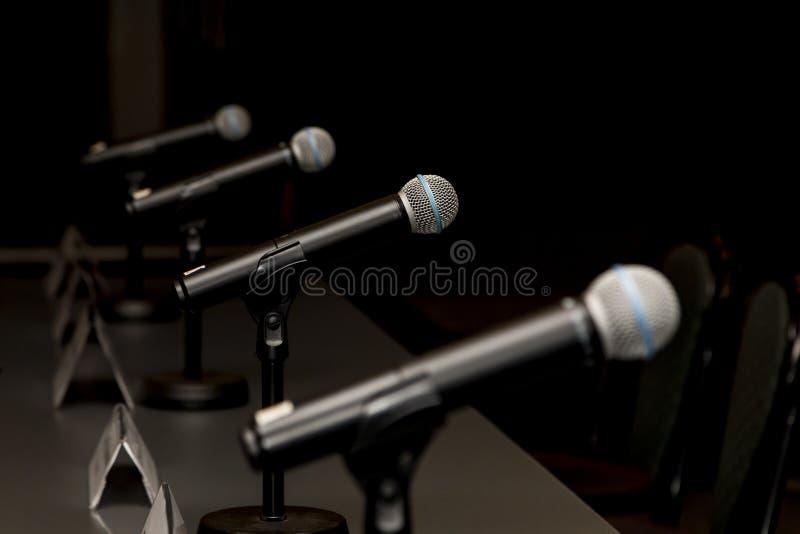 Microfoons in persconferentieruimte stock afbeeldingen