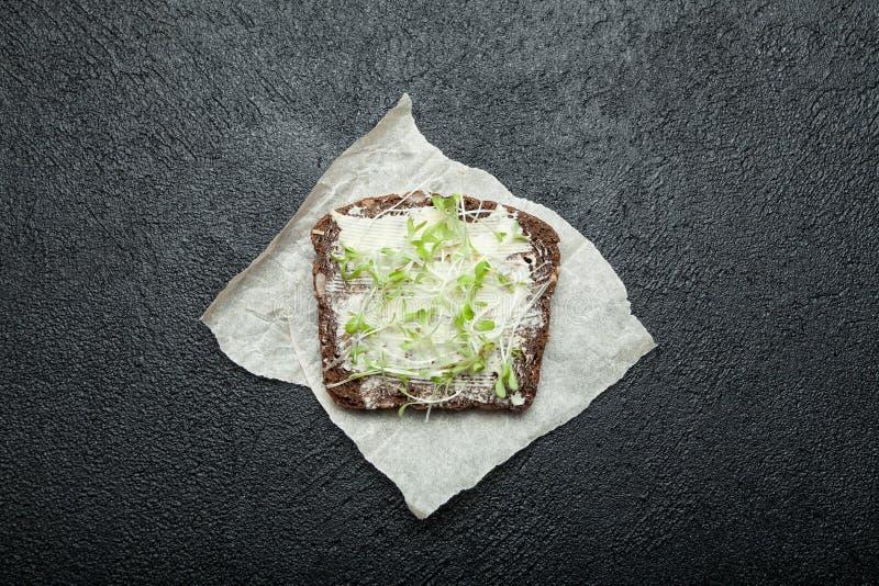 Microgreens su un pezzo di pane nero Alimento dietetico per perdita di peso e salute, calorie minime immagine stock