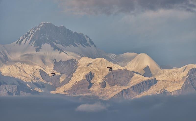 Microlight die over het Himalayagebergte vliegen stock fotografie