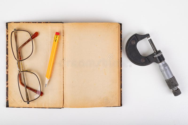 Micrometer and old book with glasses on a white table. Workshop accessories royalty free stock photos