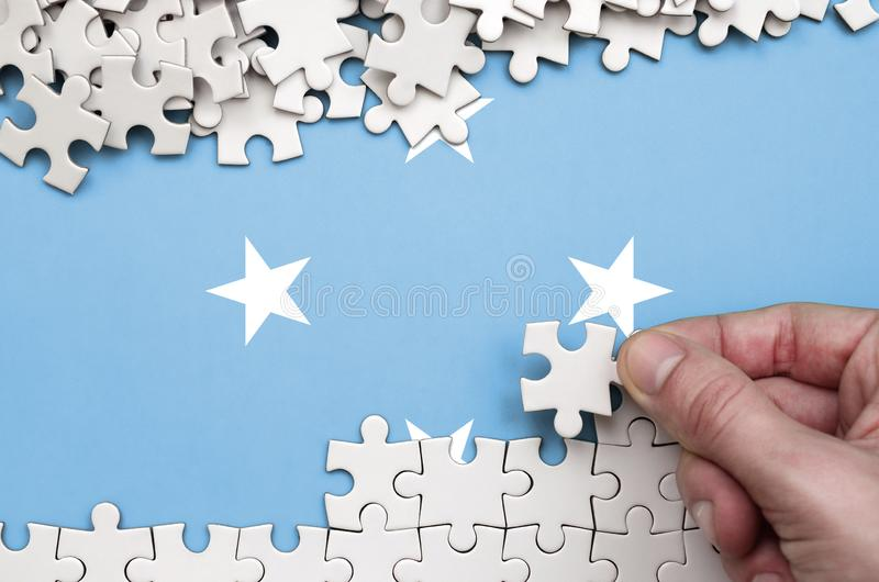 Micronesia flag is depicted on a table on which the human hand folds a puzzle of white color royalty free stock photo