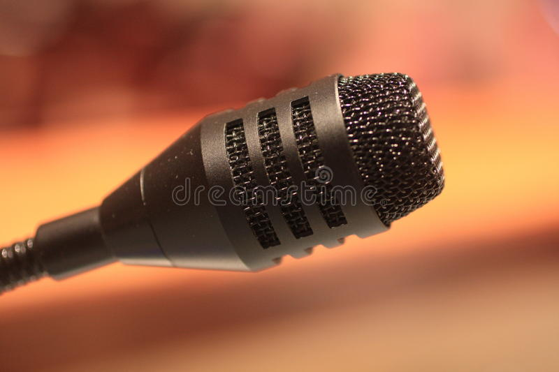 Microphone. A microphone is a device used with sound systems to speak into causing the sound to be amplified stock photography