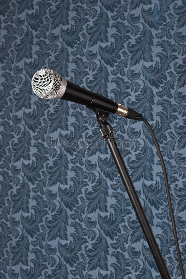 Microphone. On a stand against a busy wallpaper royalty free stock photos