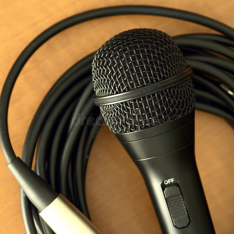 Microphone. Black microphone and cord on a wood table stock images