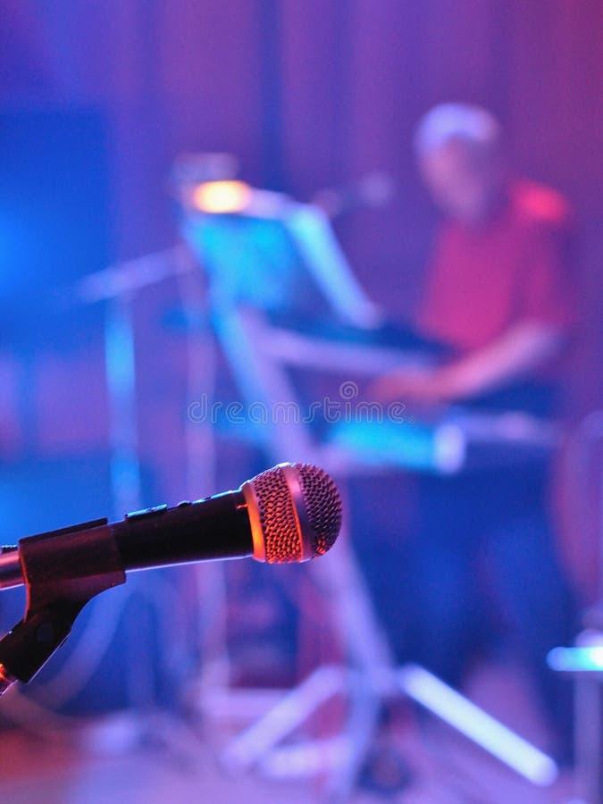 Microphone avec le pianiste brouillé à l'arrière-plan photographie stock libre de droits
