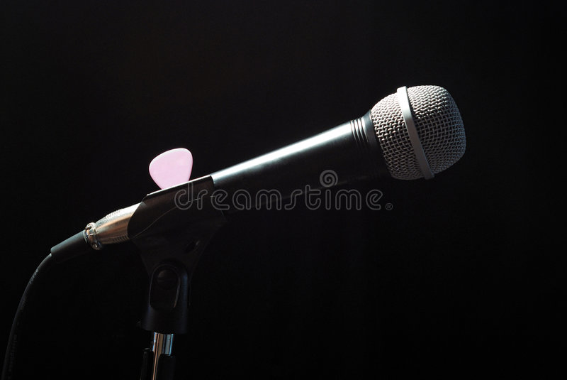 Microphone on the bar. Top down illuminated music microphone on the bar with a pick and cable - still life stock photos
