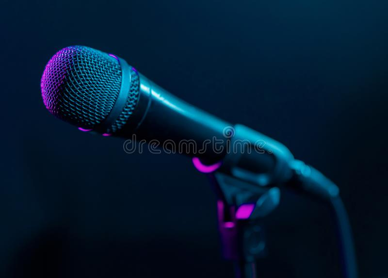 Microphone on black background with colorful pink and turquoise light. Music, concert concept. stock photography