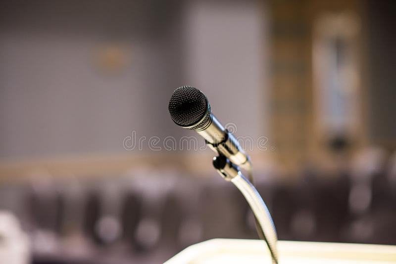 Microphone on blurred in seminar room or conference hall background royalty free stock photography