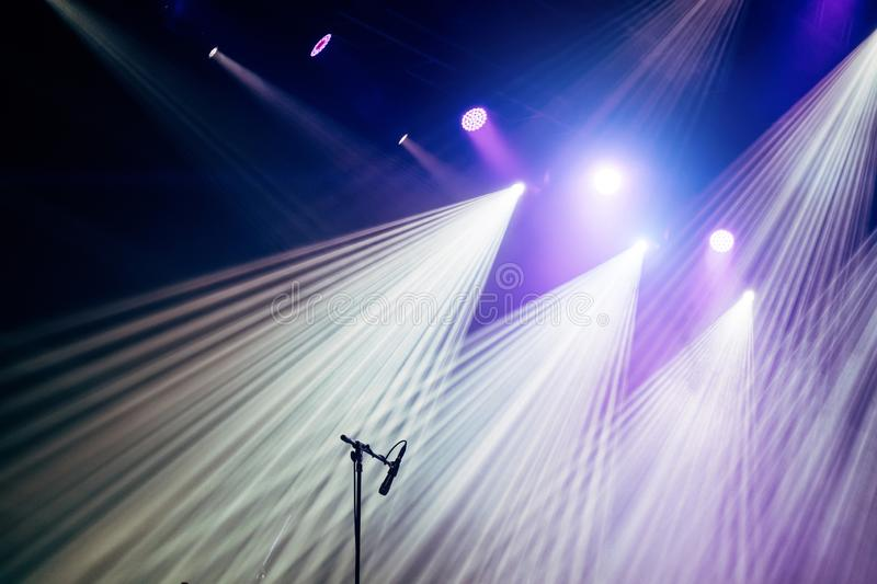 Microphone and bright rays of light on stage before the concert begins.  stock photo