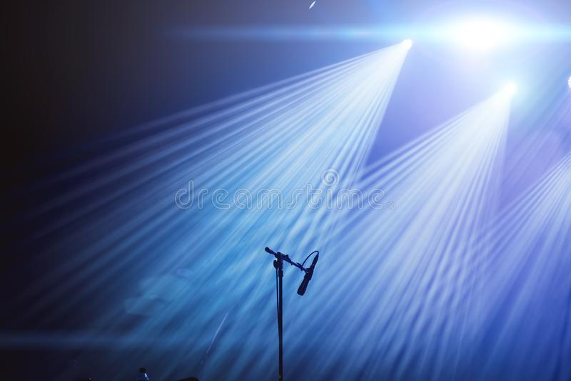 Microphone and bright rays of light on stage before the concert begins.  royalty free stock photos