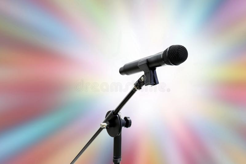 Microphone close up shot on blurred soft gradient zoom colorful effect light pink blue shade bokeh abstract background, party Sing. Microphone close up on stock photo