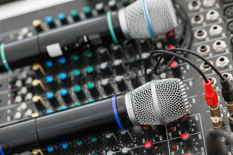 Microphone close-up. Focus on mic. Event concept. Music mixer equalizer console for mixer control sound device. Sound stock image