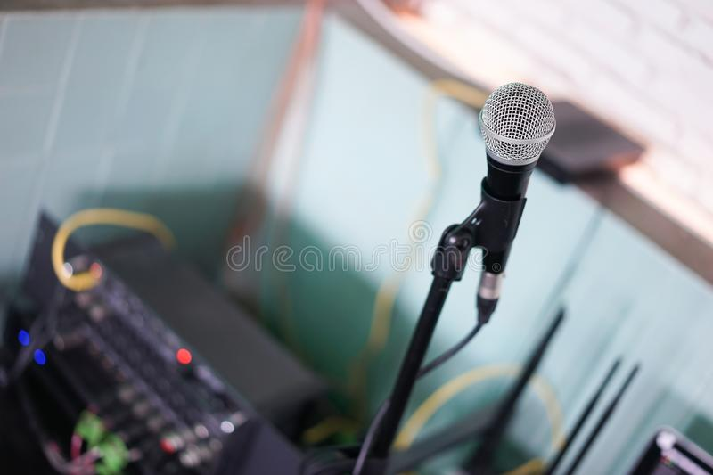Microphone. A closed up details and soft focus of a microphone with abstract blurred background of brick wall and other sound stock image