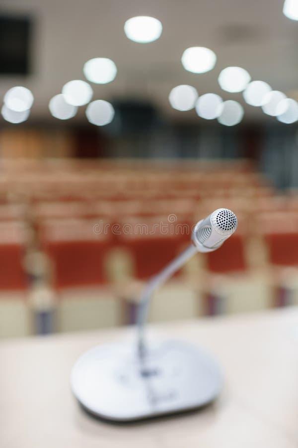 Microphone dans le premier plan Présentation de séminaire Salle de conférence complètement des sièges vides Couleur rouge Hall po photo stock