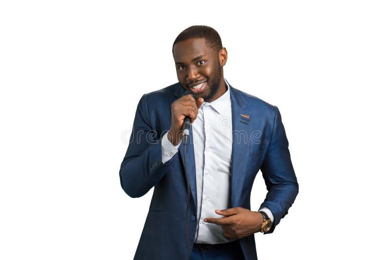 Microphone de sourire de prise d'homme de couleur photo libre de droits