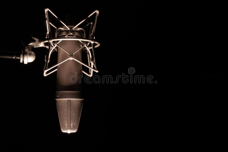 Microphone detail in music and sound recording studio, black background, closeup. Microphone detail in music and sound recording studio, black background stock photo