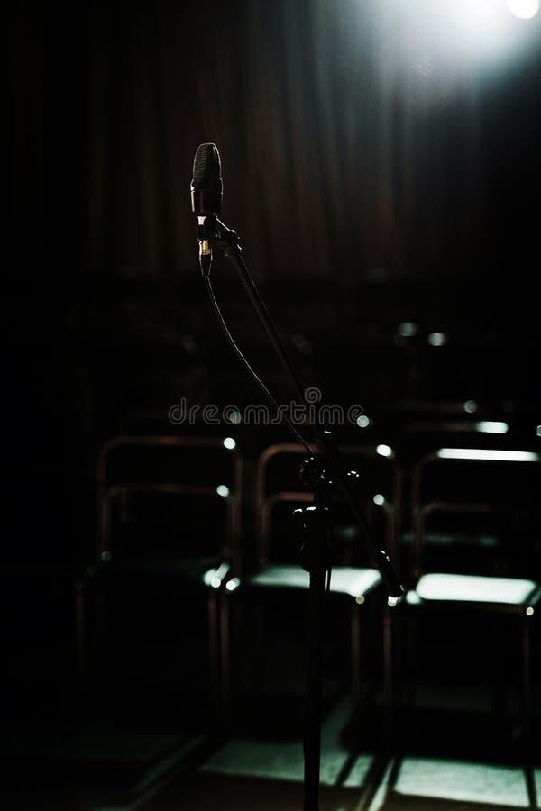 Microphone devant des rangées vides dans le petit hall foncé photo libre de droits