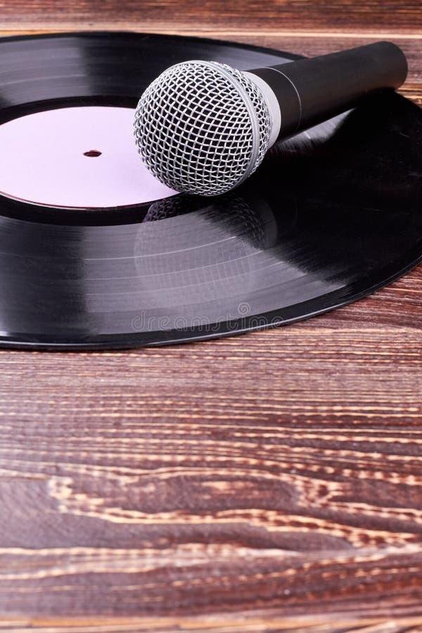Microphone et disque vinyle gris sur le fond en bois photographie stock