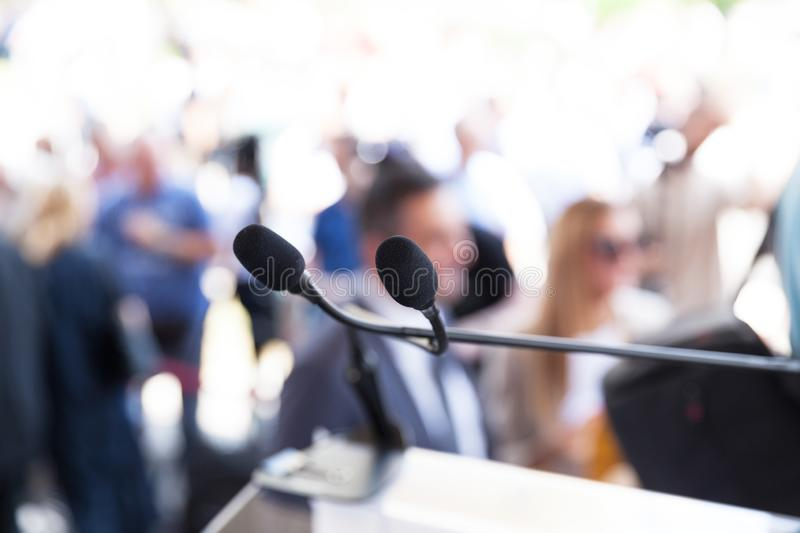 Microphone in focus at media or public event, blurred people in the background. Microphone in focus at media or public event, blurred participants in the royalty free stock photography