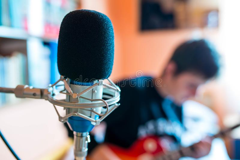 Microphone on focus, playing young guitarist on background in a small music studio. Shallow depth of field royalty free stock images