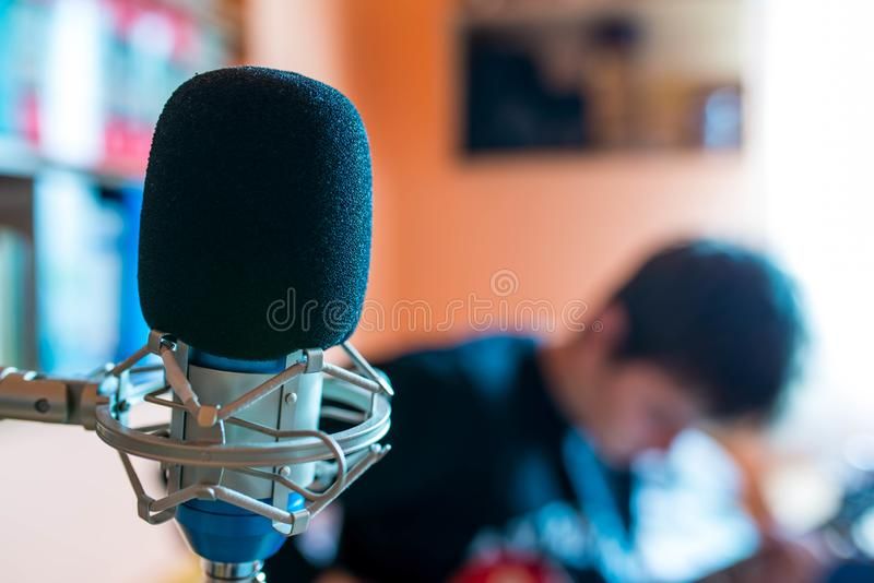 Microphone on focus, playing young guitarist on background in a small music studio. Shallow depth of field stock photo