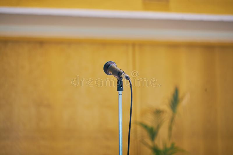 Microphone in the foreground with neutral background. Picture taken in a modern church, Event Background. Concept, voice, teacher, communication, university royalty free stock photography