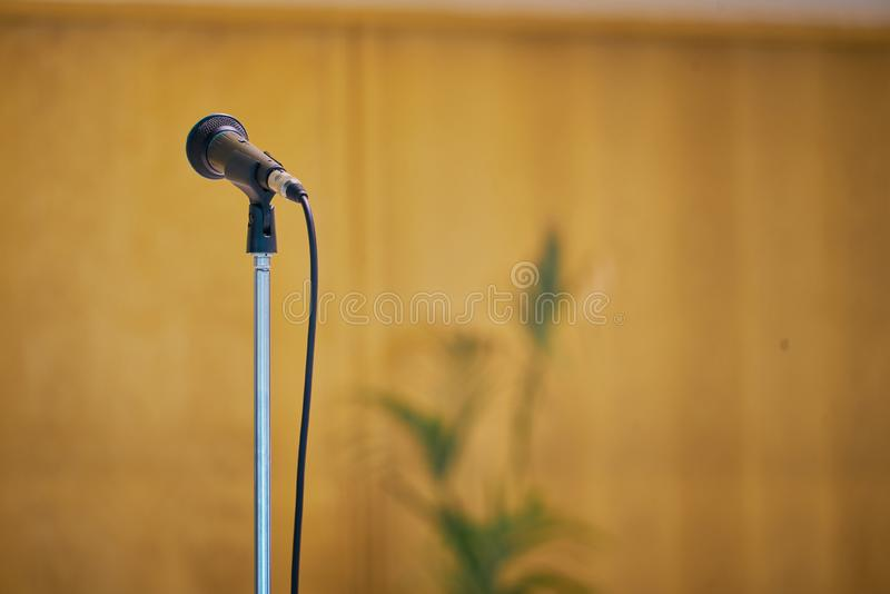 Microphone in the foreground with neutral background. Picture taken in a modern church, Event Background. Concept, voice, teacher, communication, university royalty free stock photos